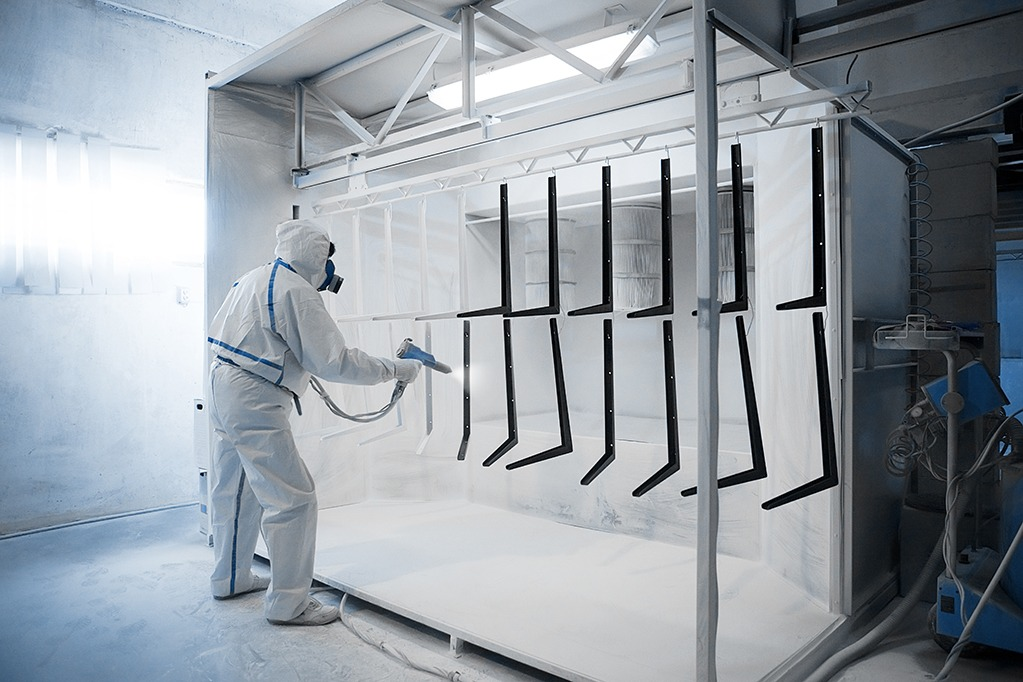 Worker wearing protective wear performing powder coating of metal details in a special industrial camera
